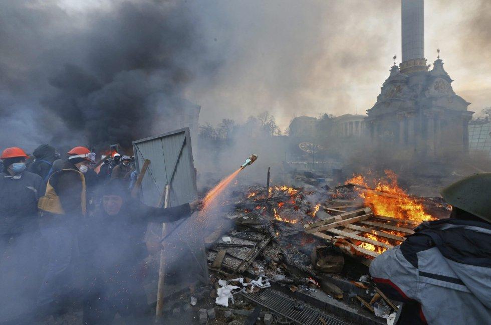 Manifestantes disparam um projétil contra os policiais durante os protestos violentos no centro de Kiev nesta quarta-feira.