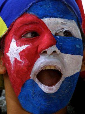 Uma mulher com a bandeira cubana pintada no rosto em frente à embaixada de  Cuba na 33fca25c8d0
